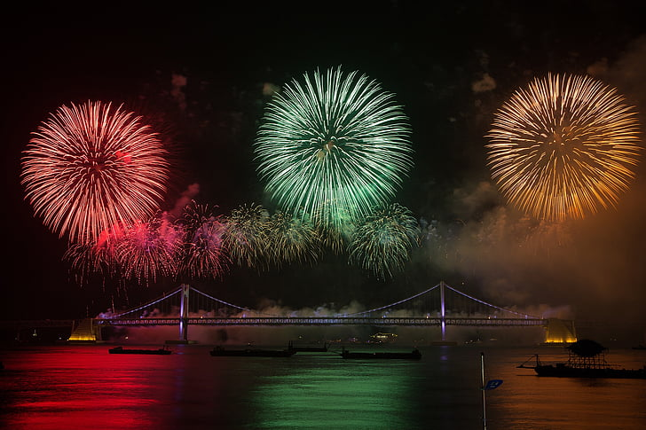 Fireworks under the bridge with boats on body of water