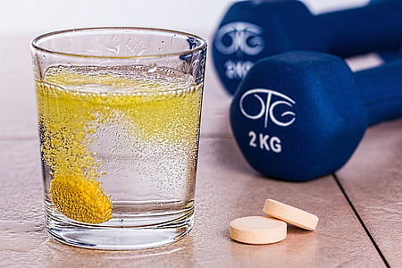 clear rock glass beside two white medication tablets near pair of 2 kg blue fixed dumbbells