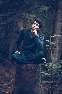 man sitting on tree stump