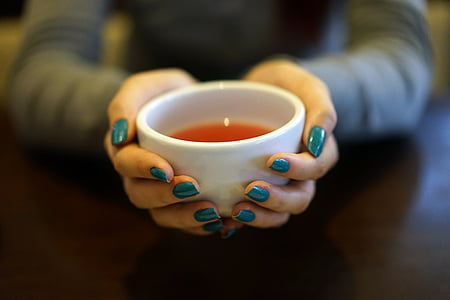 person with teal manicure holding white ceramic bowl