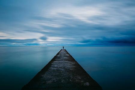 man standing at the edge of breakwater bridge