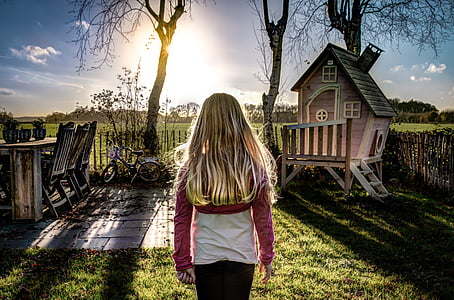 girl standing near wooden playhouse