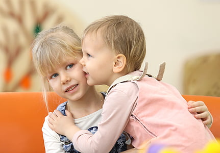 girl and toddler talking to each other