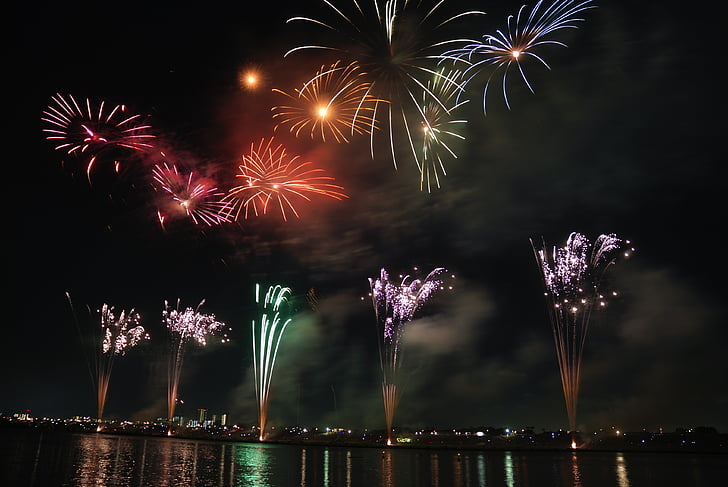 city lights near body of water with fireworks display