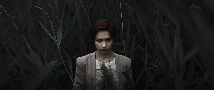 woman in gray blazer surrounded by grass