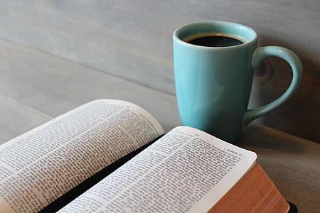 teal ceramic mug near white book