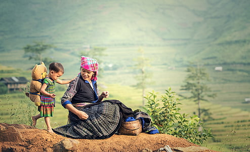 selective focus photography of girl carrying bear plush toy near woman sitting on hill