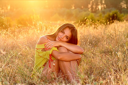 woman in yellow dress sitting on green grass during daytime