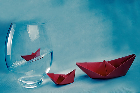 two red origami boats beside clear glass fish bowl filled with water