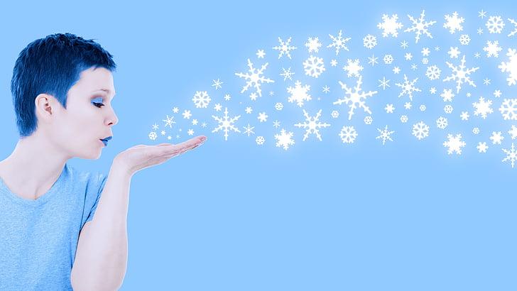 woman blowing snowflakes