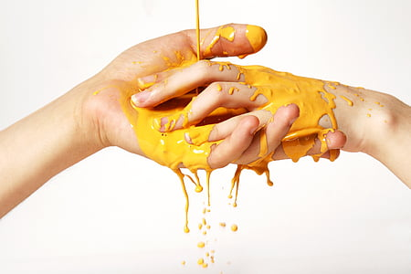 two person hands soaked in yellow liquid