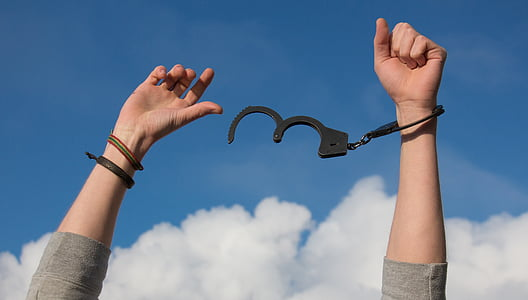 person freeing a handcuff with a view of blue sky