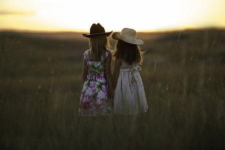 two girl wearing hats watching sunrise during daytime