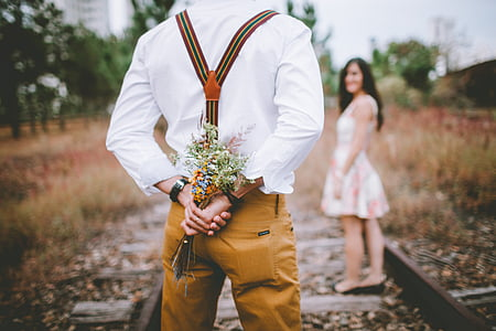 man holding flowers in front of woman during daytime