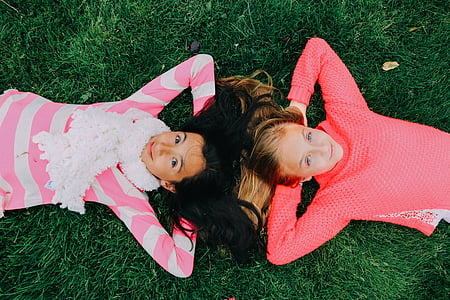 two girls wearing pink and white long-sleeved shirts lying on grass during daytime