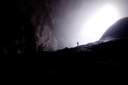 person standing on cave