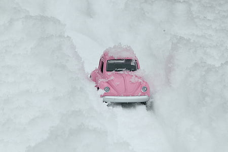 pink Volkswagen Beetle scale model on snow