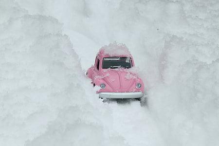 pink Volkswagen Beetle scale model on snow