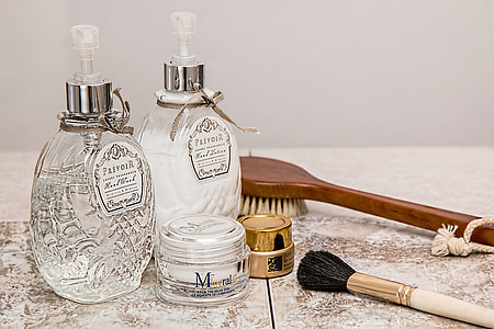 close-up of two fragrance bottles, makeup brush, and face powder on beige surface