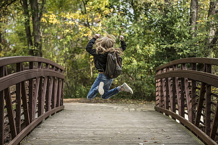 girl jump shot photo on brown wooden bridge