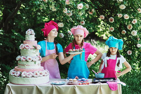 three girls baking cake near trees