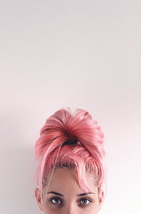 woman in pink hair beside white wall
