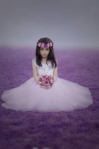 girl wearing white dress holding bouquet of flower