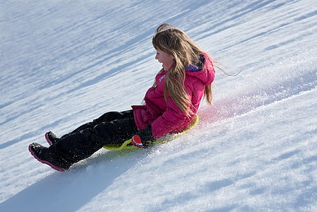 woman in pink bubble hoodie riding green sled