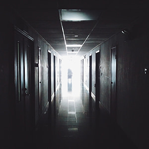 person in middle of hallway behind the light