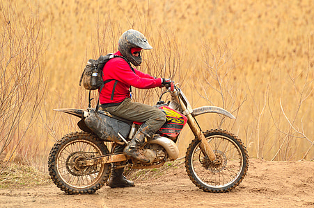 man in red jacket and grey pants riding on dirt bike