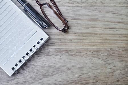 steno notebook beside black pen and brown framed eyeglasses