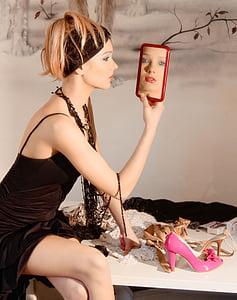 woman looking herself at the mirror wearing black spaghetti strap dress