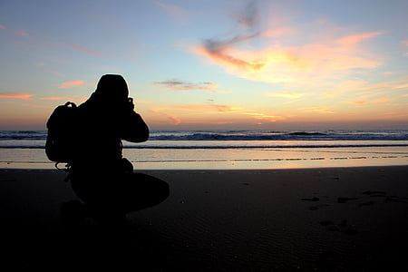 man capturing sunset on beach shore