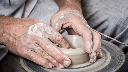 person molding gray clay pot