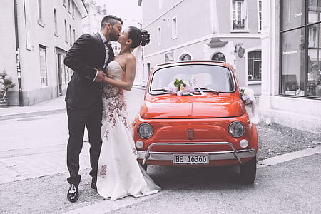new wedding couple kissing at side of red car