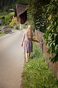 girl in dress standing on dress grass beside pathway