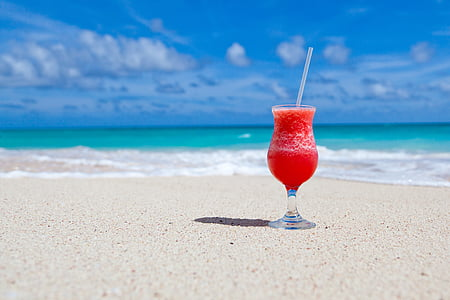 clear footed glass cup filled with smoothie on seashore