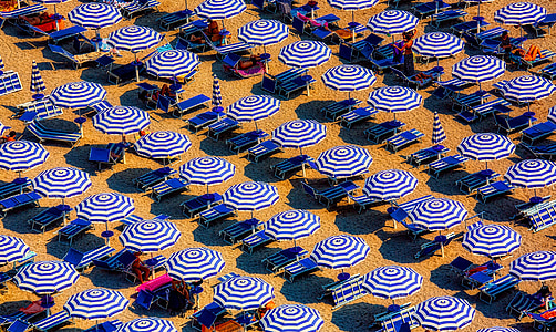 blue-and-white umbrella lot on white sand