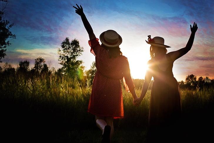 two women walking towards sunlight