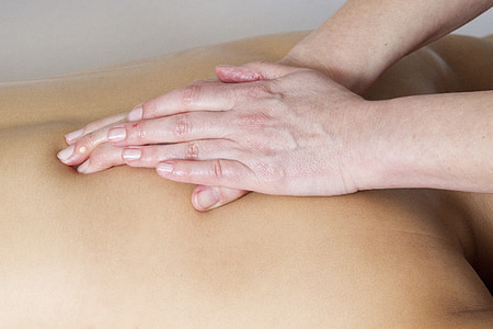 person massaging the back of another person