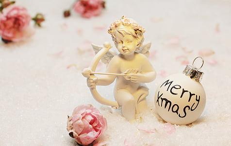 Cherub ceramic figurine beside of white Christmas ball