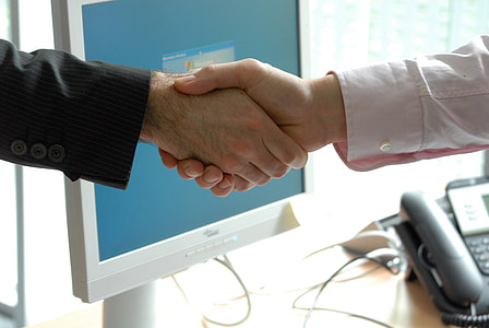 two person shaking hands beside white flat screen monitor