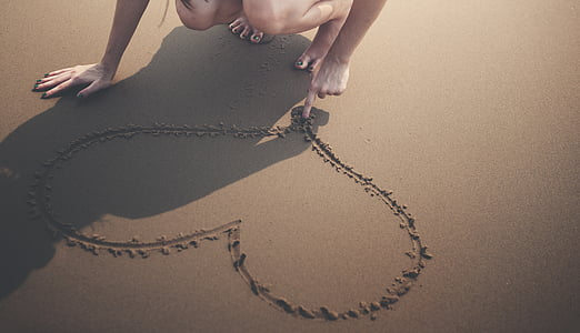 person drawing heart shape on sand