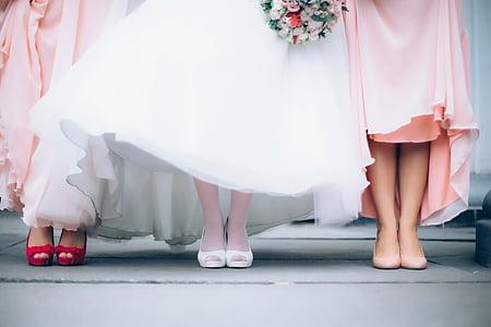 two woman wearing pink dress with woman wearing white dress