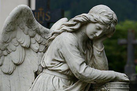 female angel leaning on column post