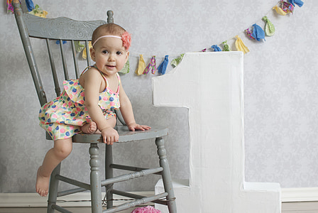 baby sitting on gray wooden chair