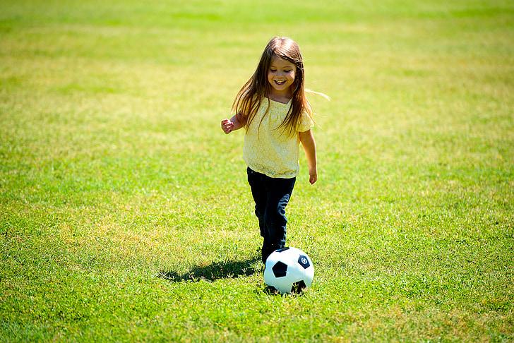 toddler girl playing soccer during daytime