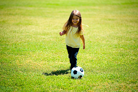 toddler girl playing soccer during daytime