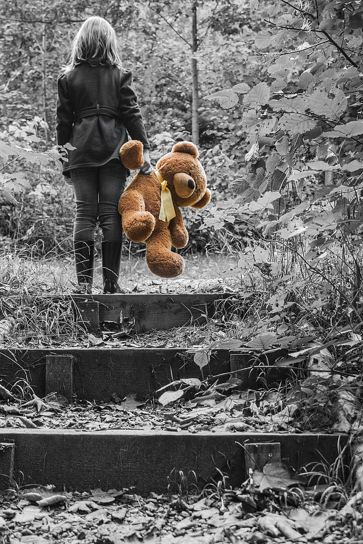selective color photography of woman holding brown bear plush toy