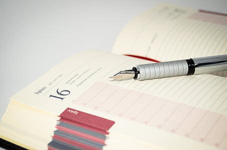 fountain pen on beige ruled notebook